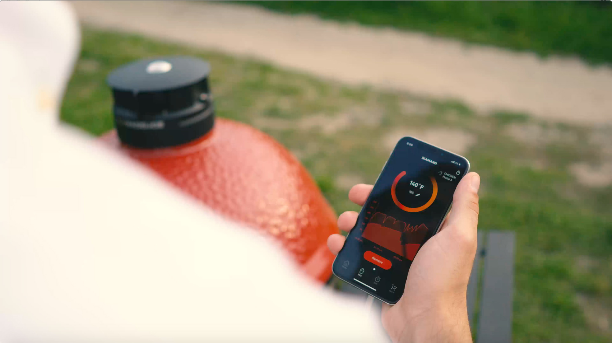 Man grilling with the iKamand app. Smart grill controller with Desora BBQ
